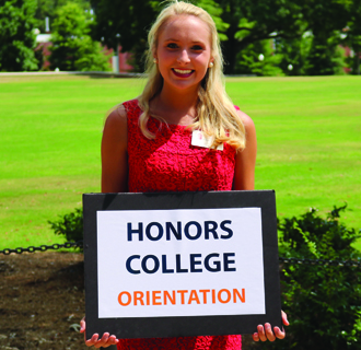 Brooklyn holding the Honors College CWE sign