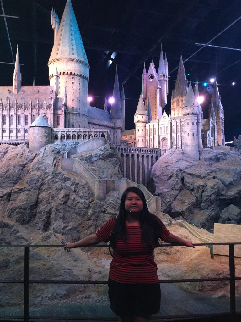 MeMe posing in front of Harry Potter set of Hogwarts.