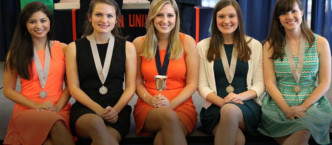 four Honors College graduates with medals on stage