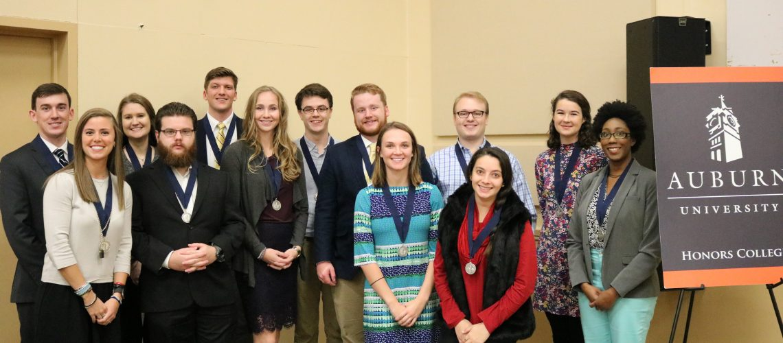 Students posing with medals by Honors College board