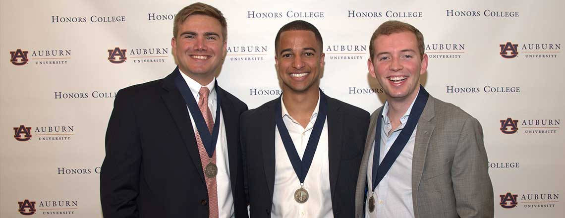 Three male Honors College graduates with their medals