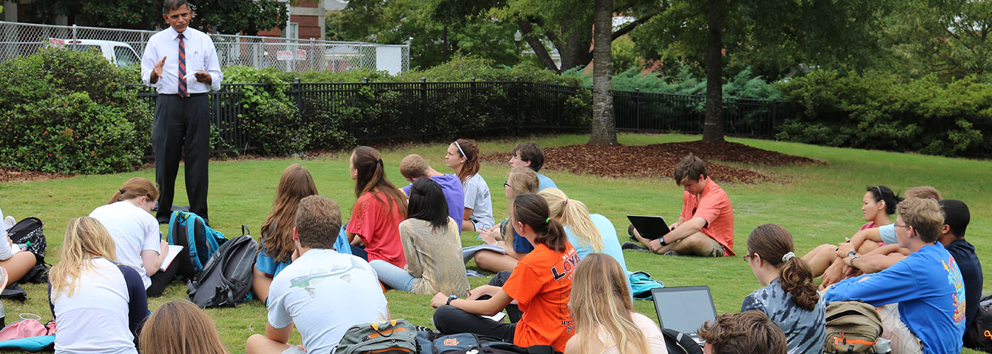 students sitting outside on cater lawn for a class