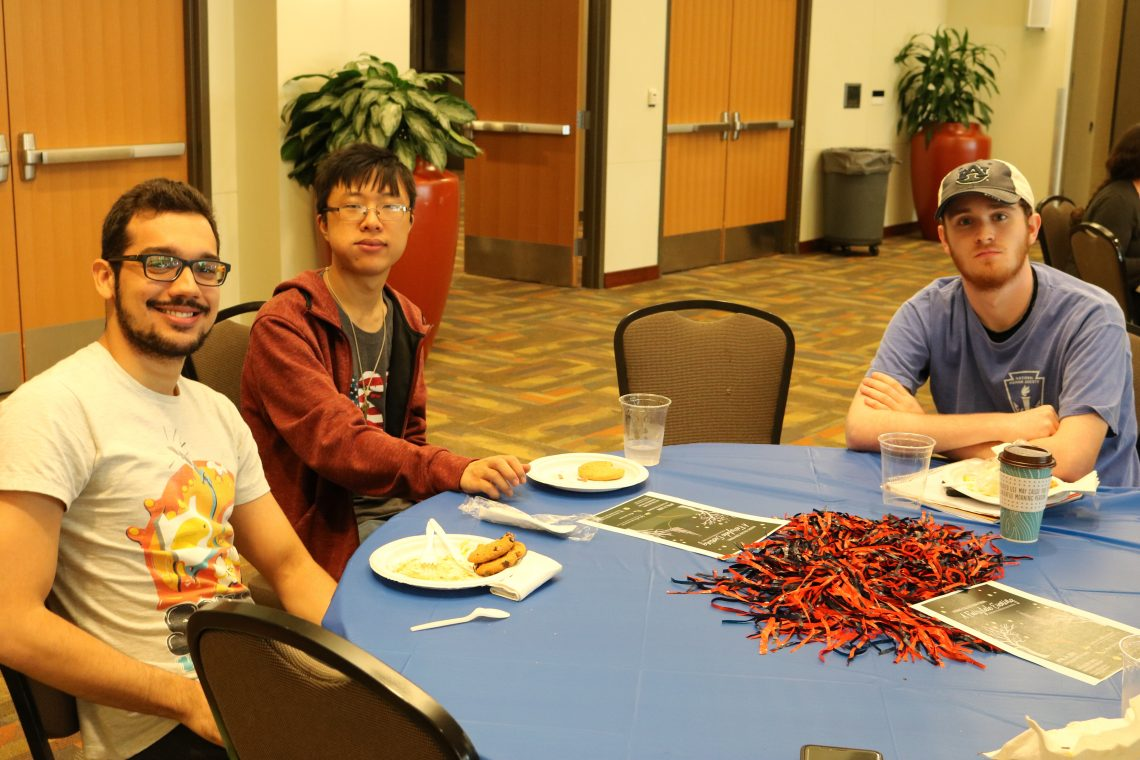 students at table eating BBQ during the mid-term picnic