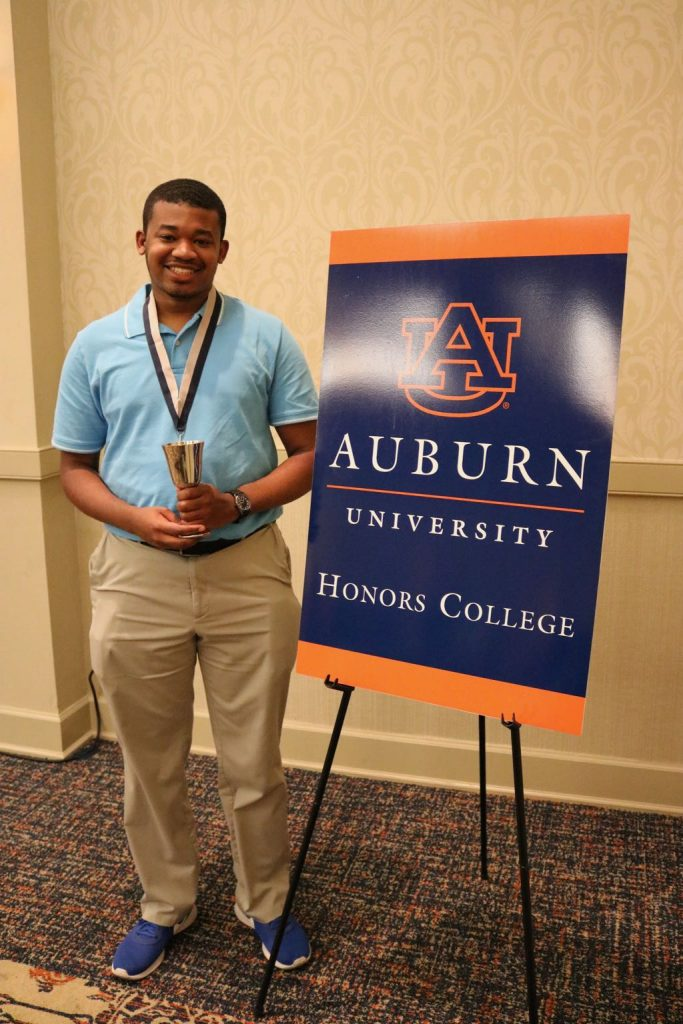 student posing in front of Honors logo with medal