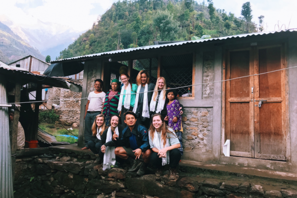 Lindsey in Nepal village with other interns and locals