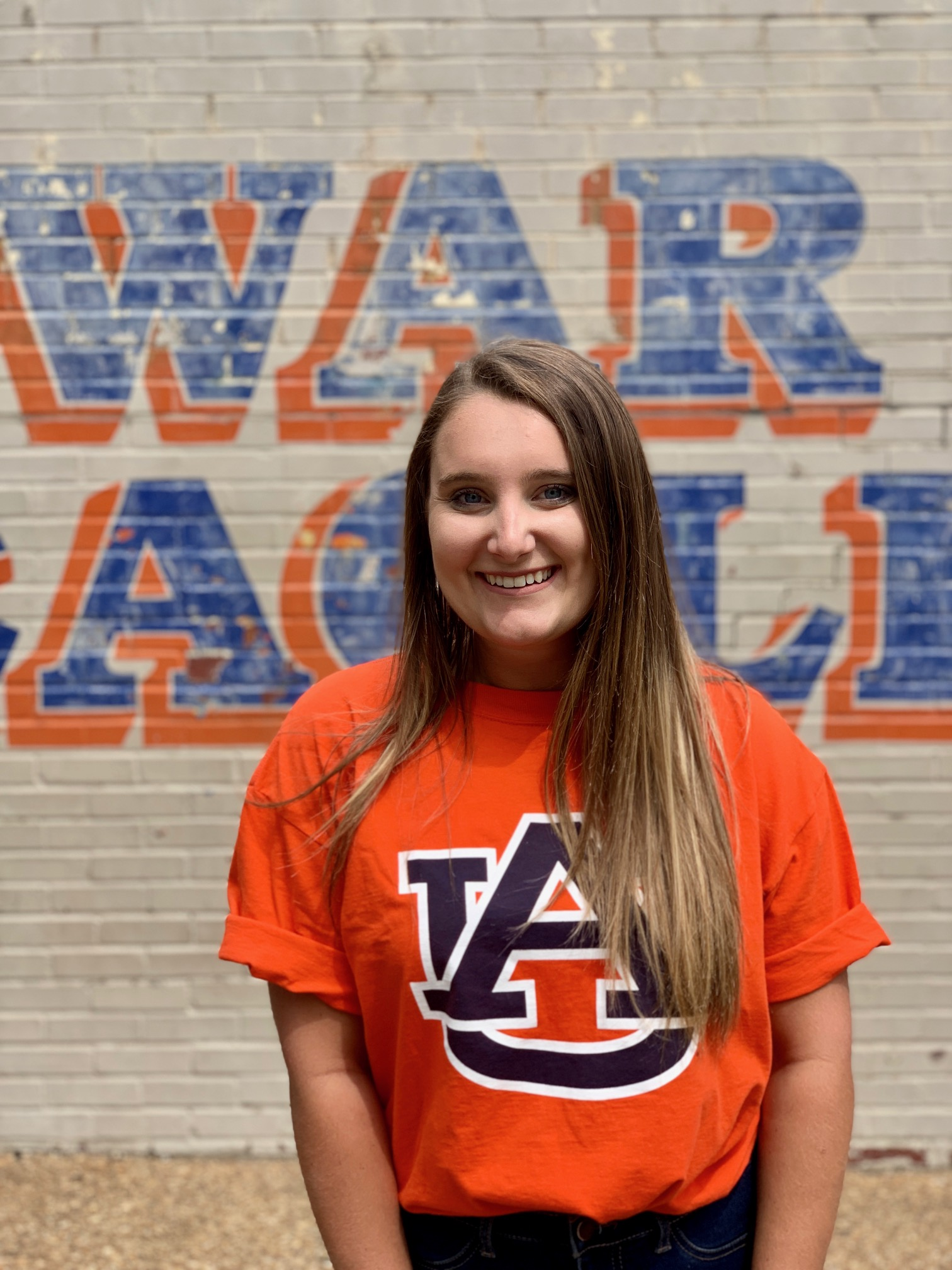 Savannah Woodall in front of War Eagle sign